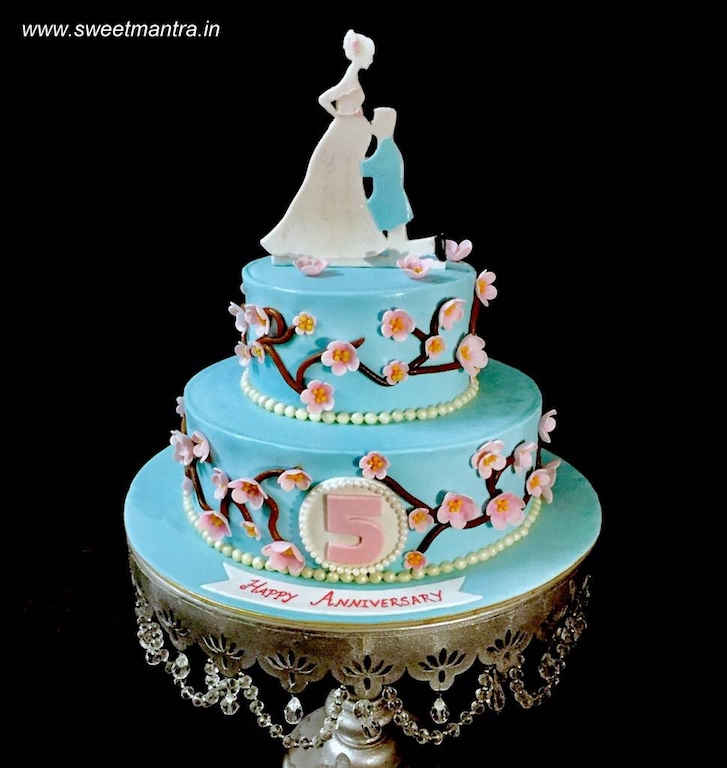 2 tier fondant cake with expecting mom for 5th anniversary in Pune