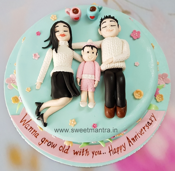 Anniversary theme designer cake with couple and newborn baby girl figurines in Pune