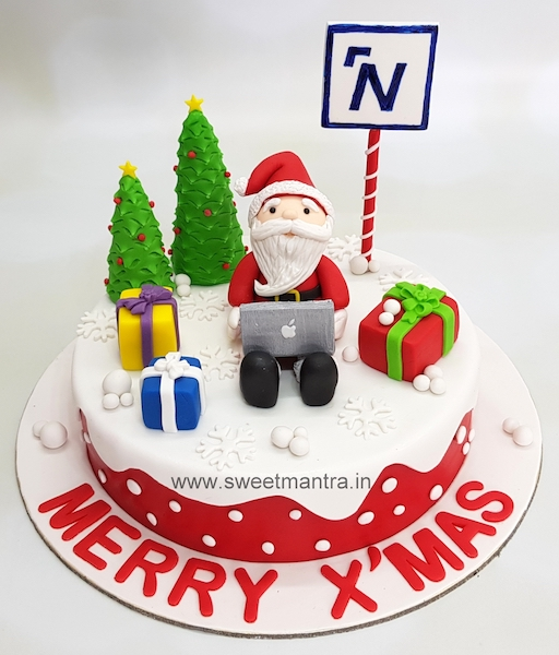 Christmas theme cake with Santa working on laptop for office celebrations at Pune